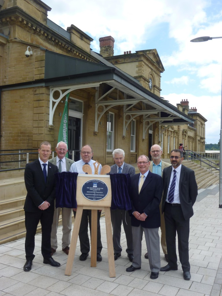 The unveiled plaque in front of the restored main building at Wakefield Kirkgate with, from left to right, Danny Fox, Assistant Operations Director for CrossRail, John Ellis, Chairman of NRHA, Stuart Baker, Department for Transport and Chairman of the BRB, Robin Leleux, Chairman of the NRHA adjudicators, Peter Cooper, Groundwork Wakefield board, Andy Savage, Director of the Railway Heritage Trust and a trustee of the NRHA, and Harj Sindhu, Corporate Services Director for Groundwork.