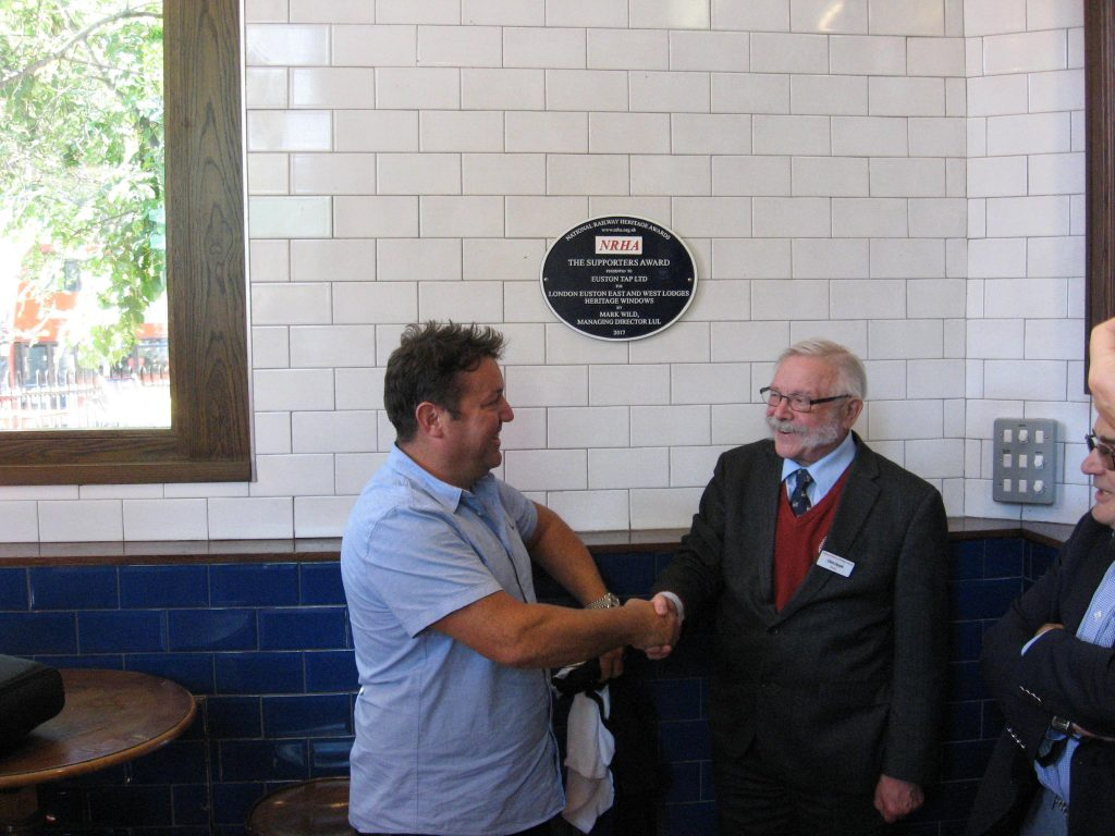 Attendees at meetings often long for the end of the debate but committee members of the National Railway Heritage Awards had a special reason for anticipating the end of the trust's committee meeting on Wednesday 26 September as the date had been set for the official unveiling of the plaque made to Euston Tap Ltd for the restored windows in the two lodges at Euston. The plaque, presented at the annual ceremony held at Merchant Taylors' Hall on 6 December 2017, recognised the project to restore the windows of the late 19th century lodges being given the Supporters Award. As was said at the ceremony 'It has been a thoroughly worthwhile enterprise for which all involved can take great credit.' 	One of the more entertaining facets of the event was the 'curtain' used to hide the plaque before its unveiling by Chris Smyth, from the Heritage Railway Association (one of the award's sponsors) – this was one of the T-shirts normally worn by the staff behind the bar.